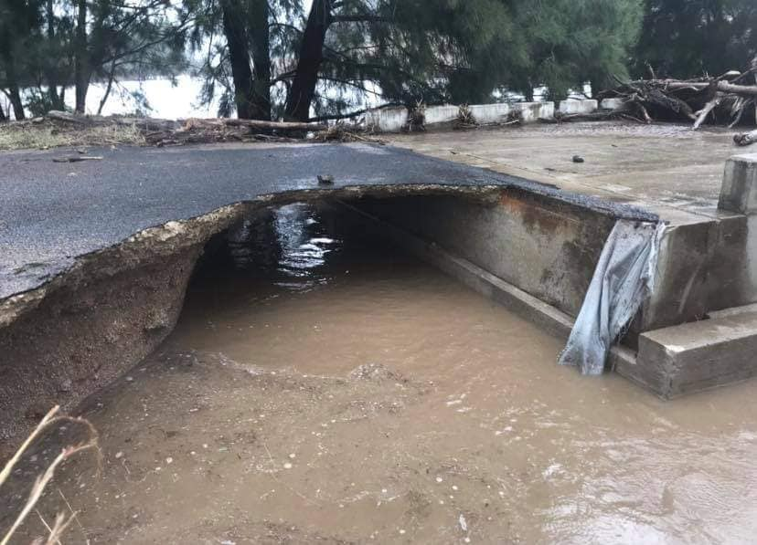 Road badly damaged by flood water.