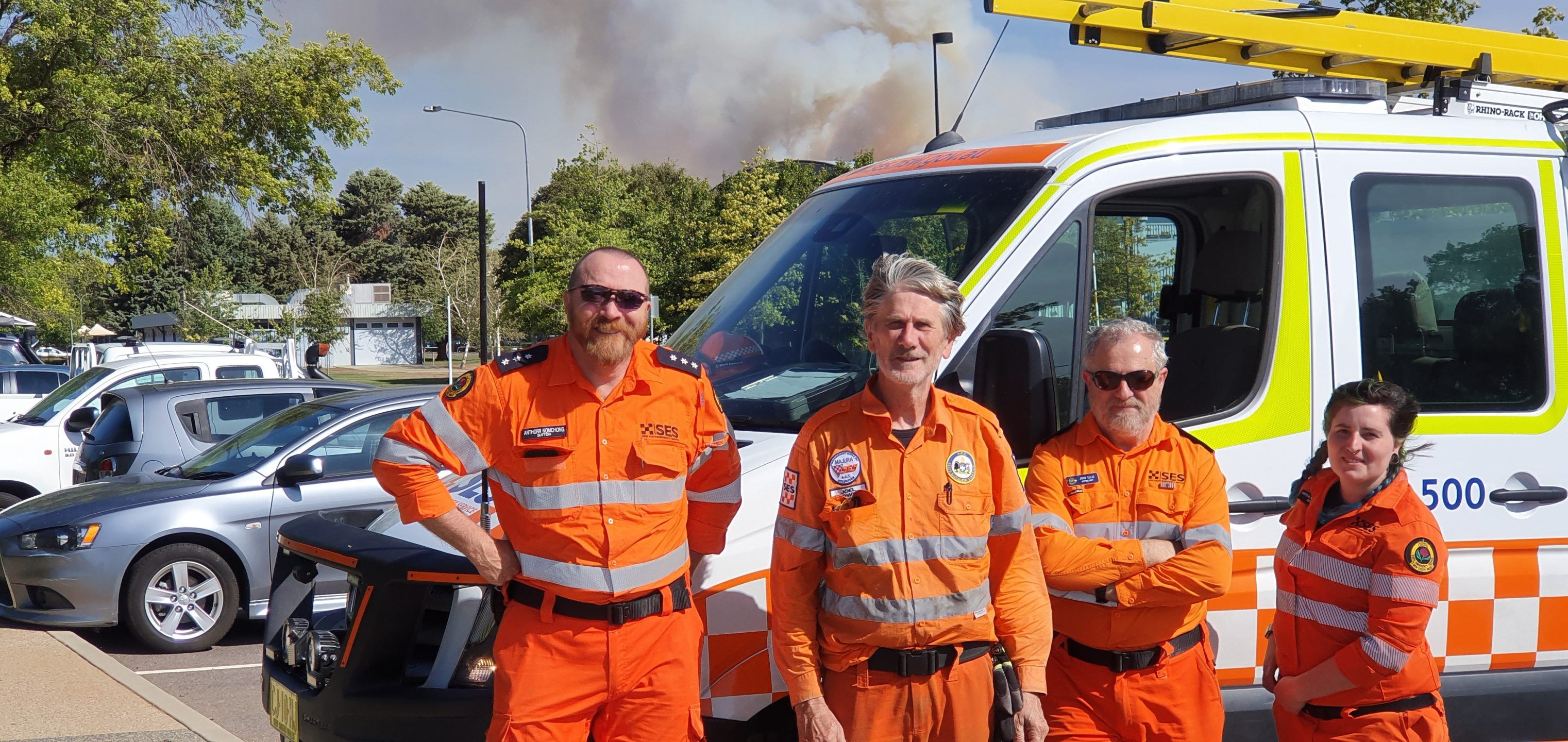 Four SES personnel standing next to an SES van. Smoke in the background