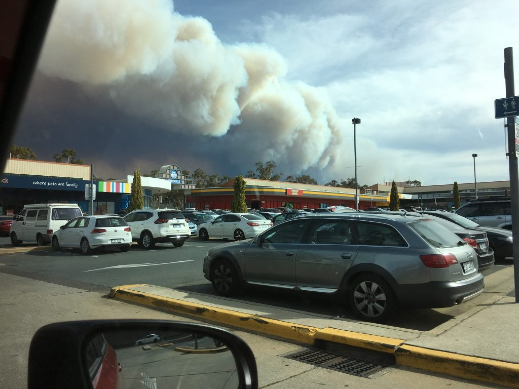 Smoke billowing over shopping centre in a car park