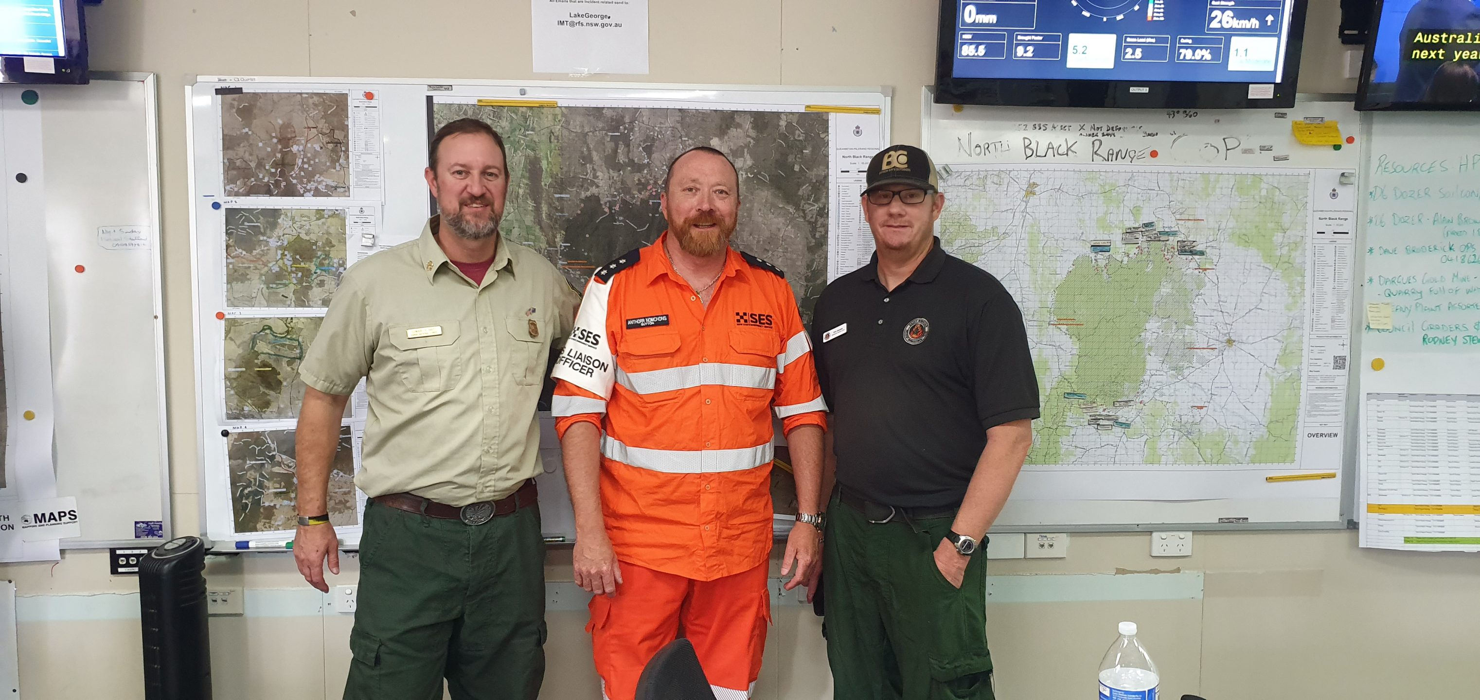 Anthor SES liaision officer standing with two USA assistance officers in a RFS office