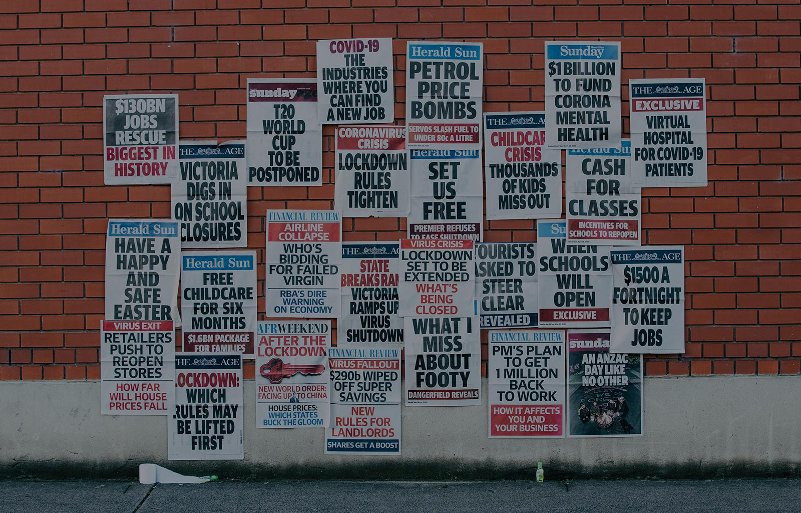 Melbourne news article headlines on a brick wall.