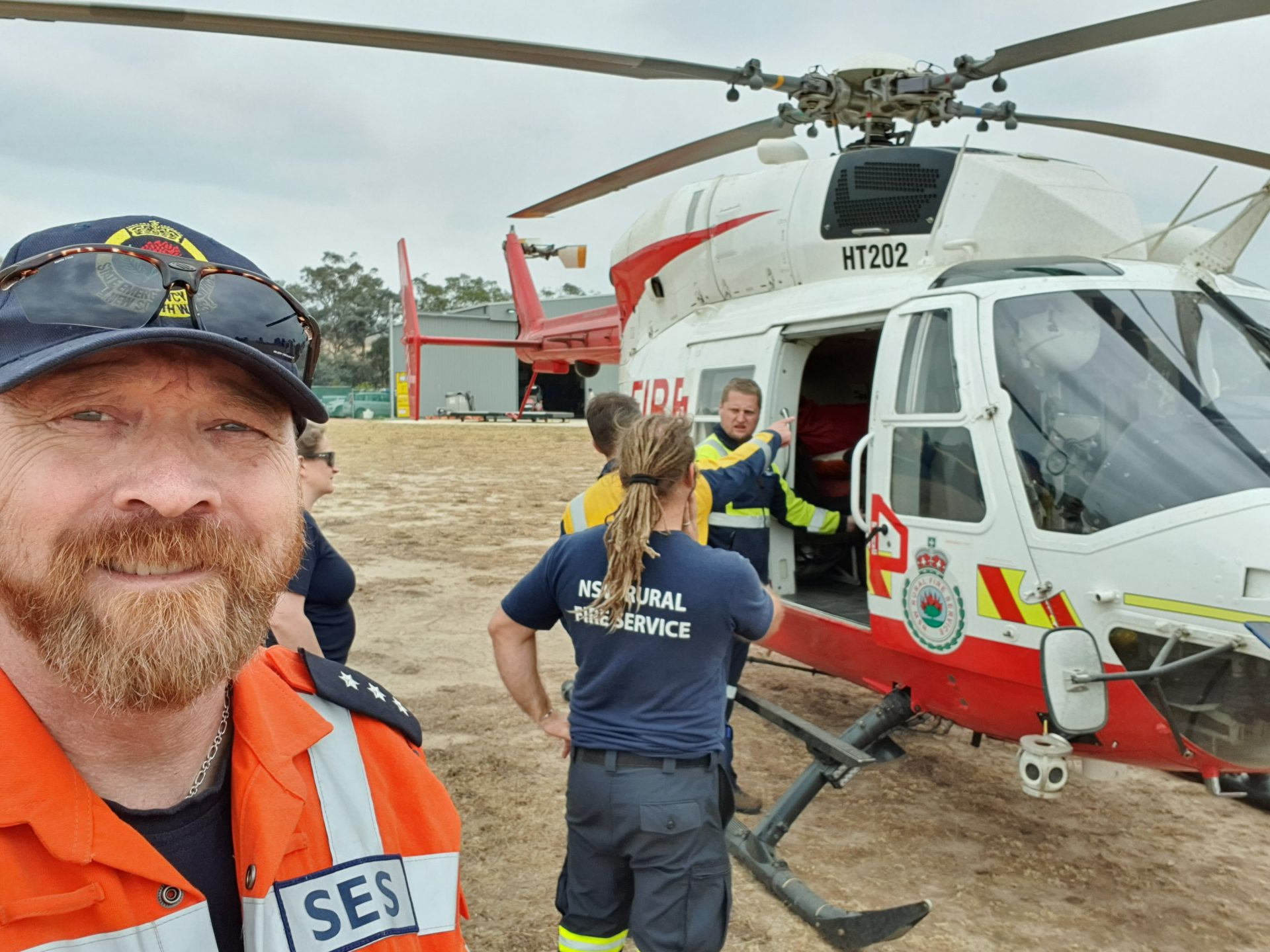Anothor taking a selfie in front of an helicopter. Three other people are looking at the helicopter.