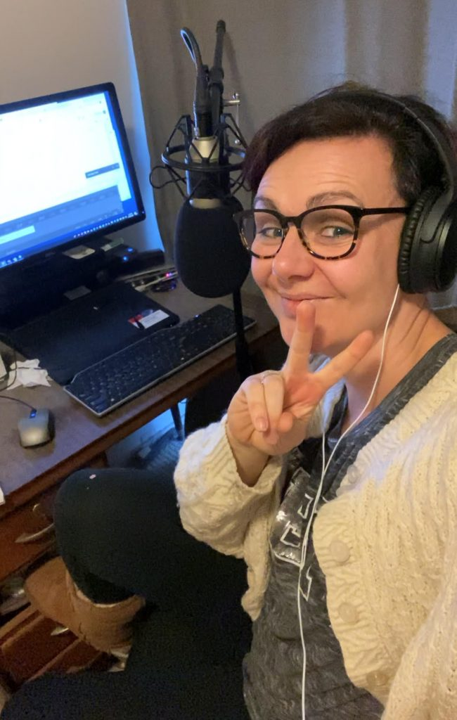 Tegan Taylor smiling showing a peace sign in front of a computer and microphone