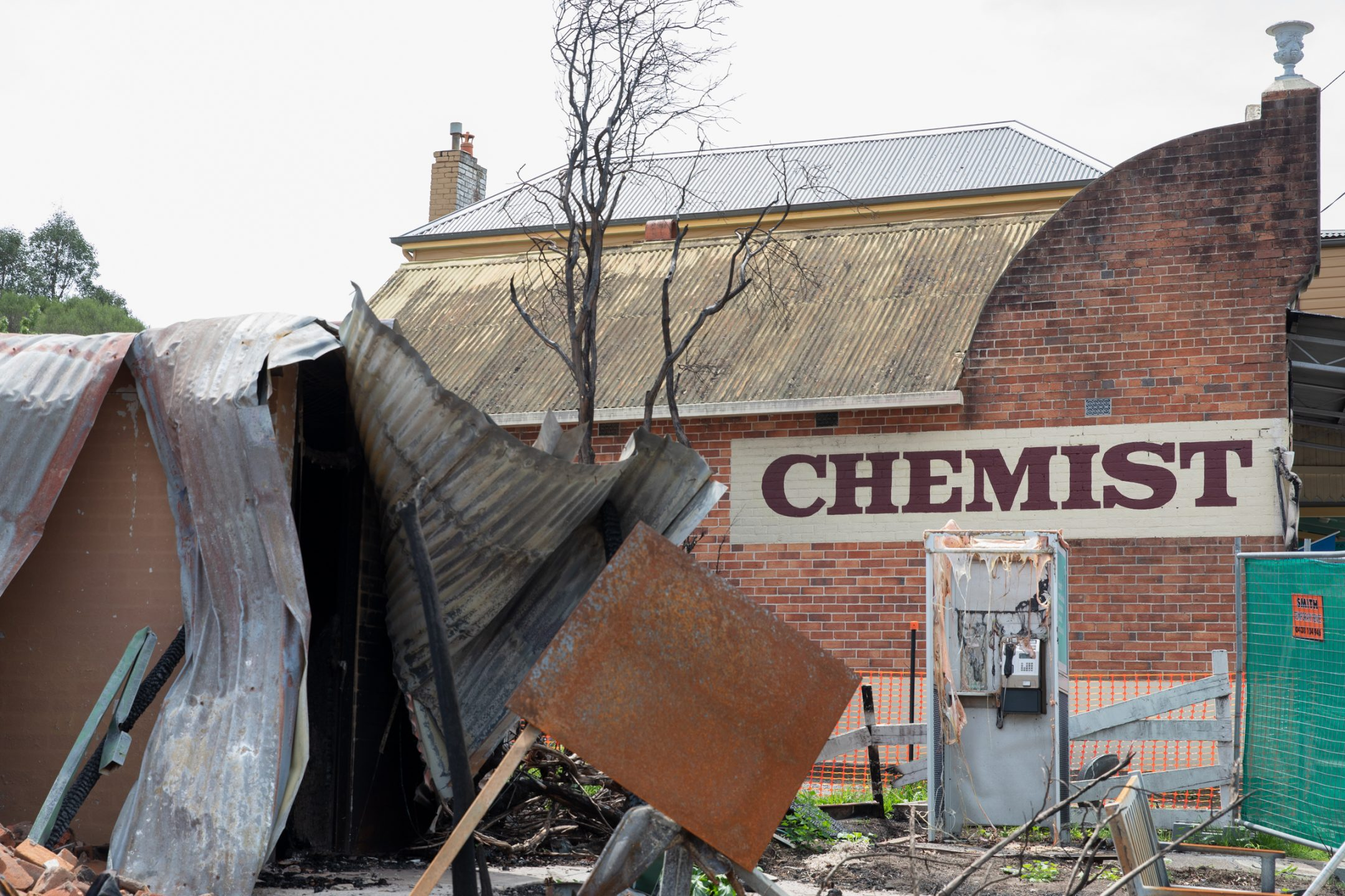 Destroyed building made with corrugated iron. Charred brick chemist building in the background