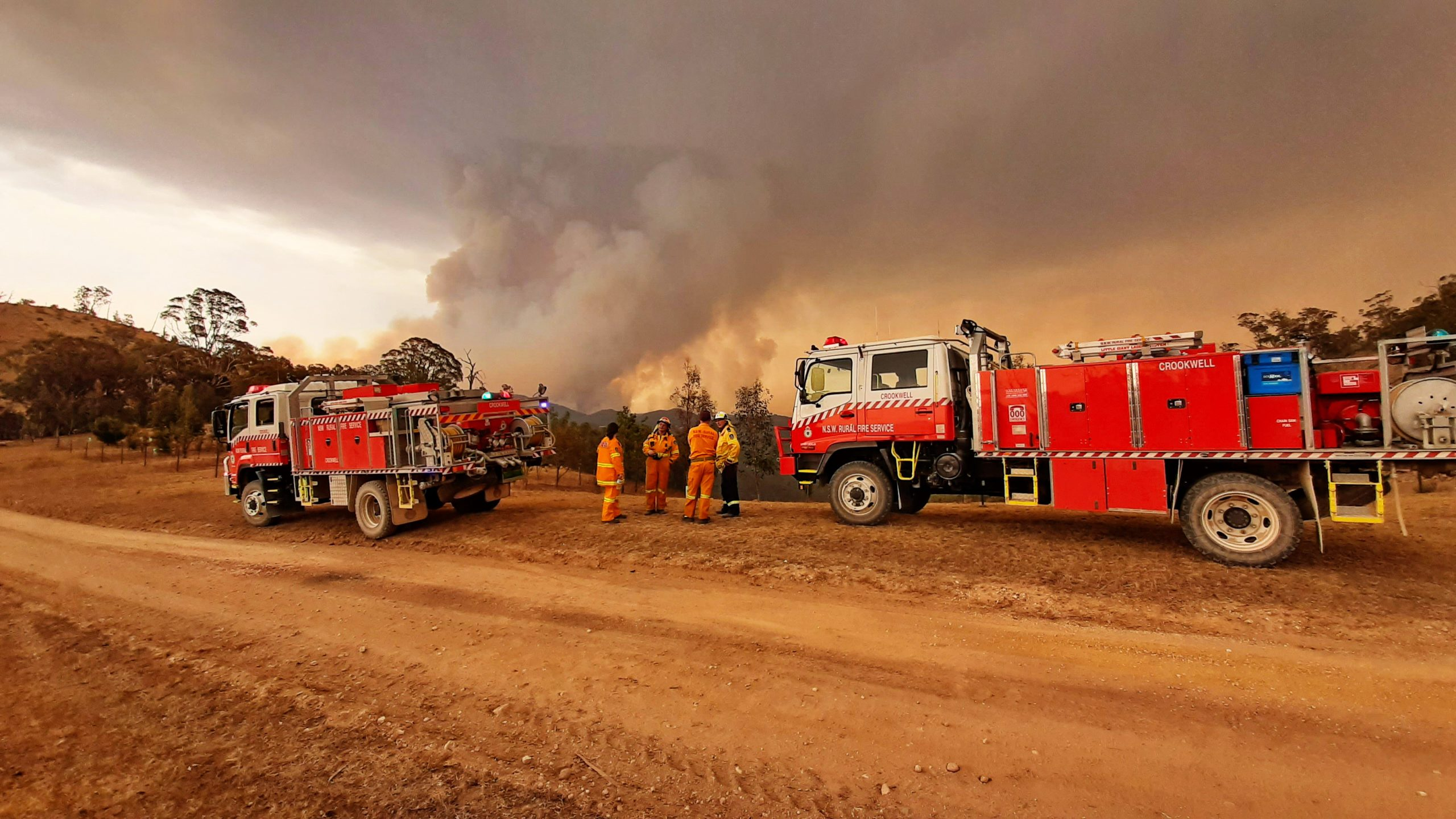Two fire engines parked on a dirt road with a large smoke plume in the distance. Four fire fighters stand next to the trucks.