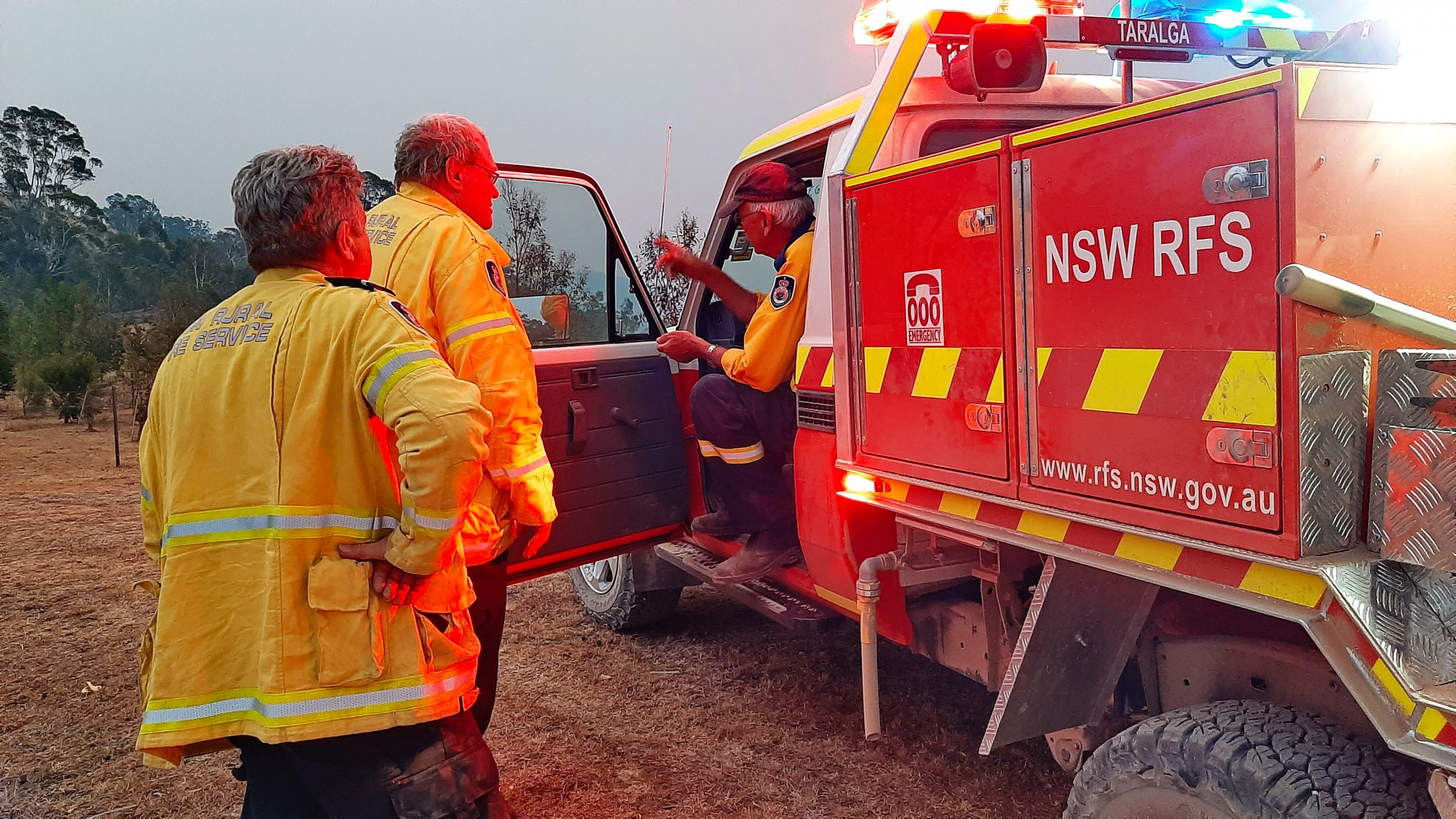 Three firefighters with a New South Wales Rural Fire Service truck. Two of them are standing next to the truck and one is in the drivers seat.