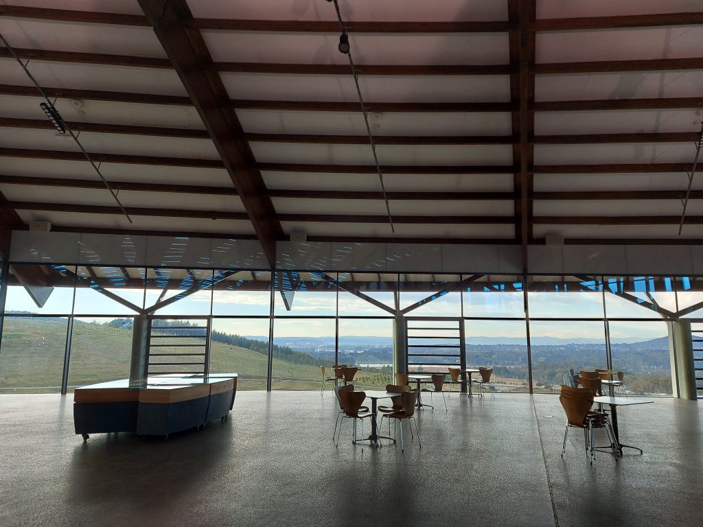 Empty visitor centre with sparse arrangement of tables and chairs