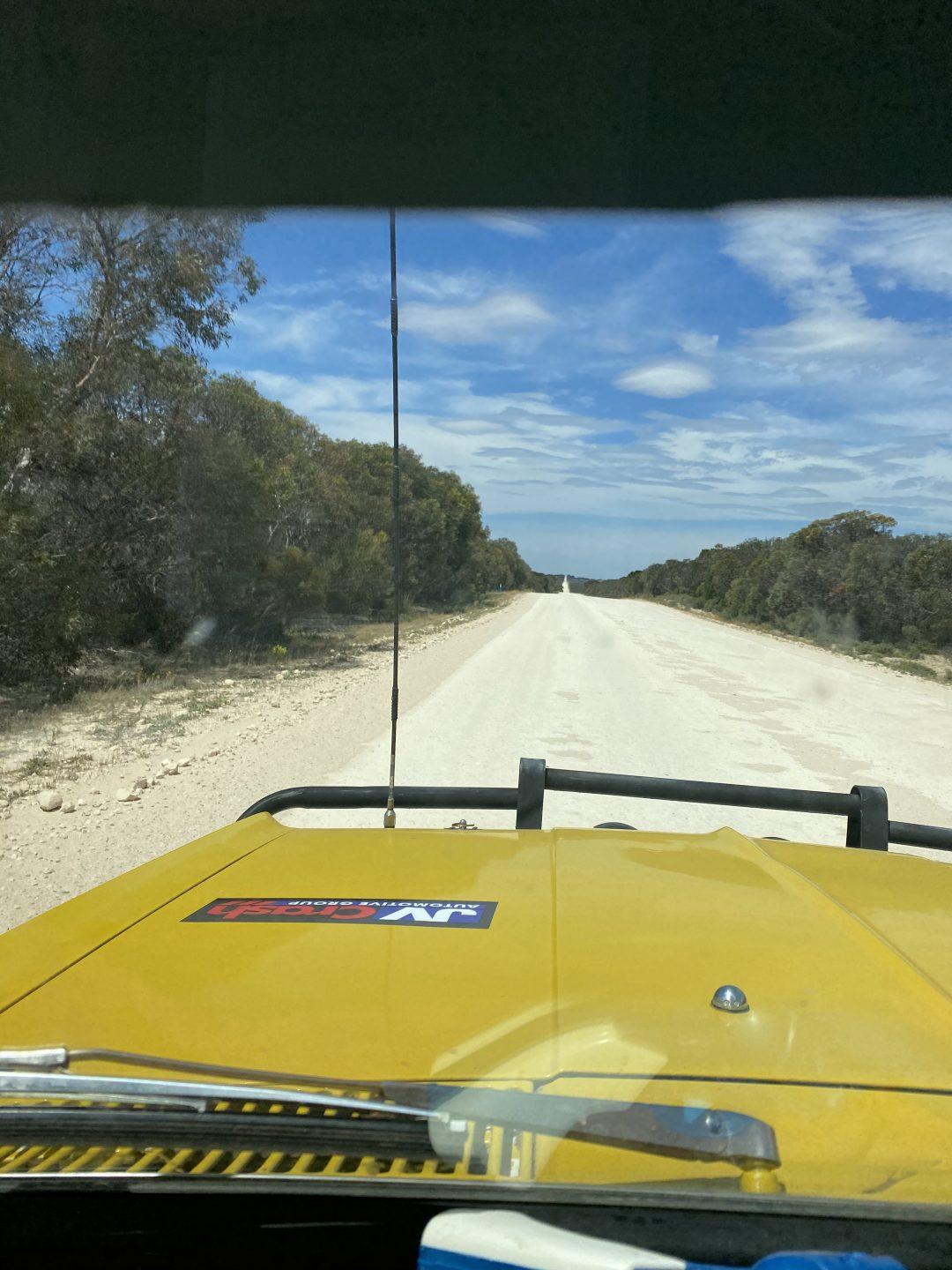 A photo taken from inside a car looking out the windscreen to a dirt road. The car bonnet is yellow and the dirt road is lined with Australian bush land.