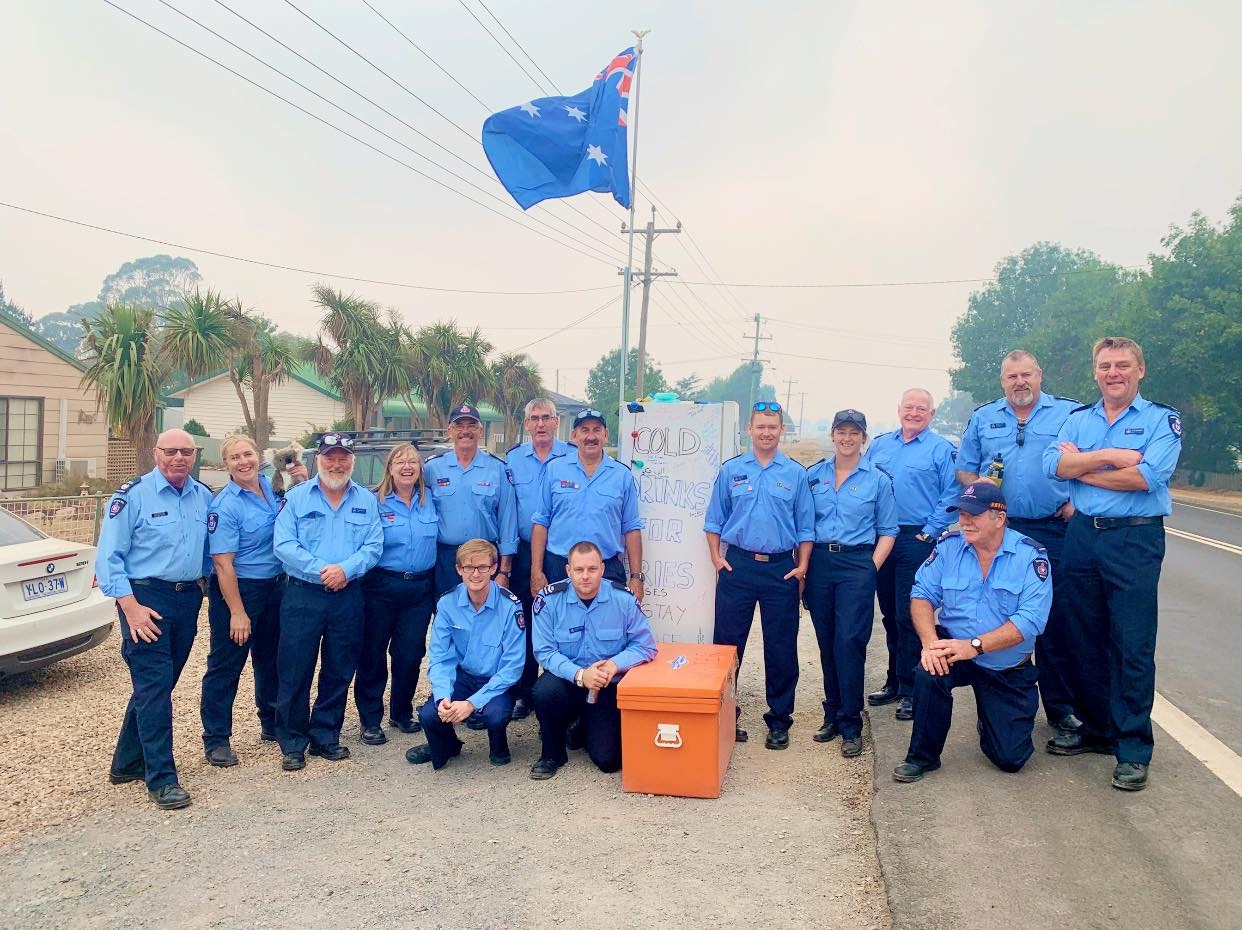 A posed photo of 15 people standing with a fridge on the side of the road. The fridge has an orange esky sitting next to it and an Australian flag attached at the top.