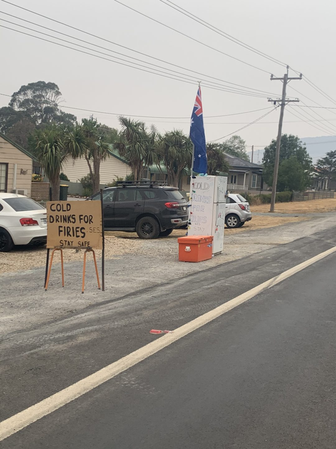 A fridge on the site of a road with an orange esky sitting next to it and an Australian flag attached to the top. A sign written on cardboard stand near it that says 'cold drinks for firies'.