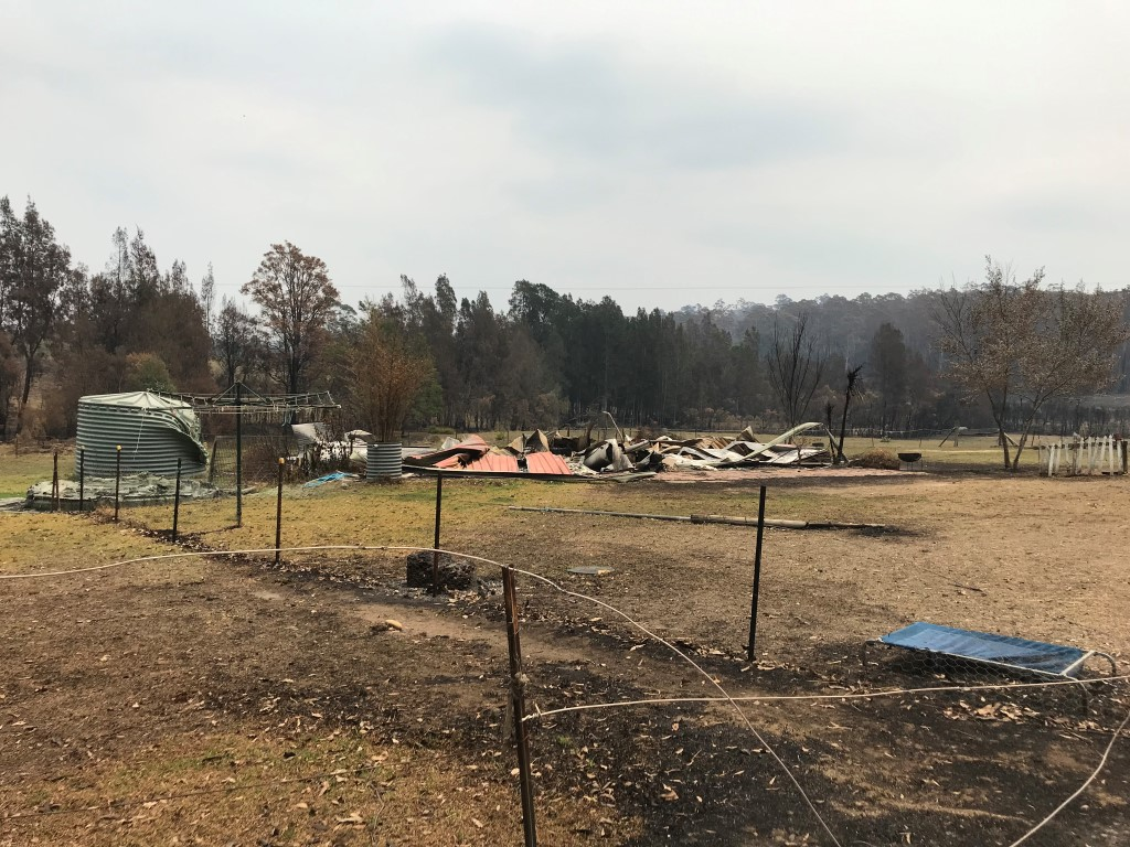 A rural property burned by a bush fire and melted water tanks