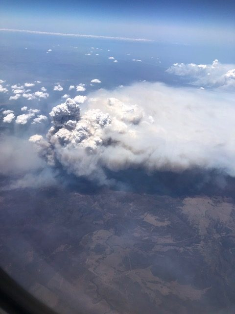 Large smoke cloud above the ground taken from a plane.