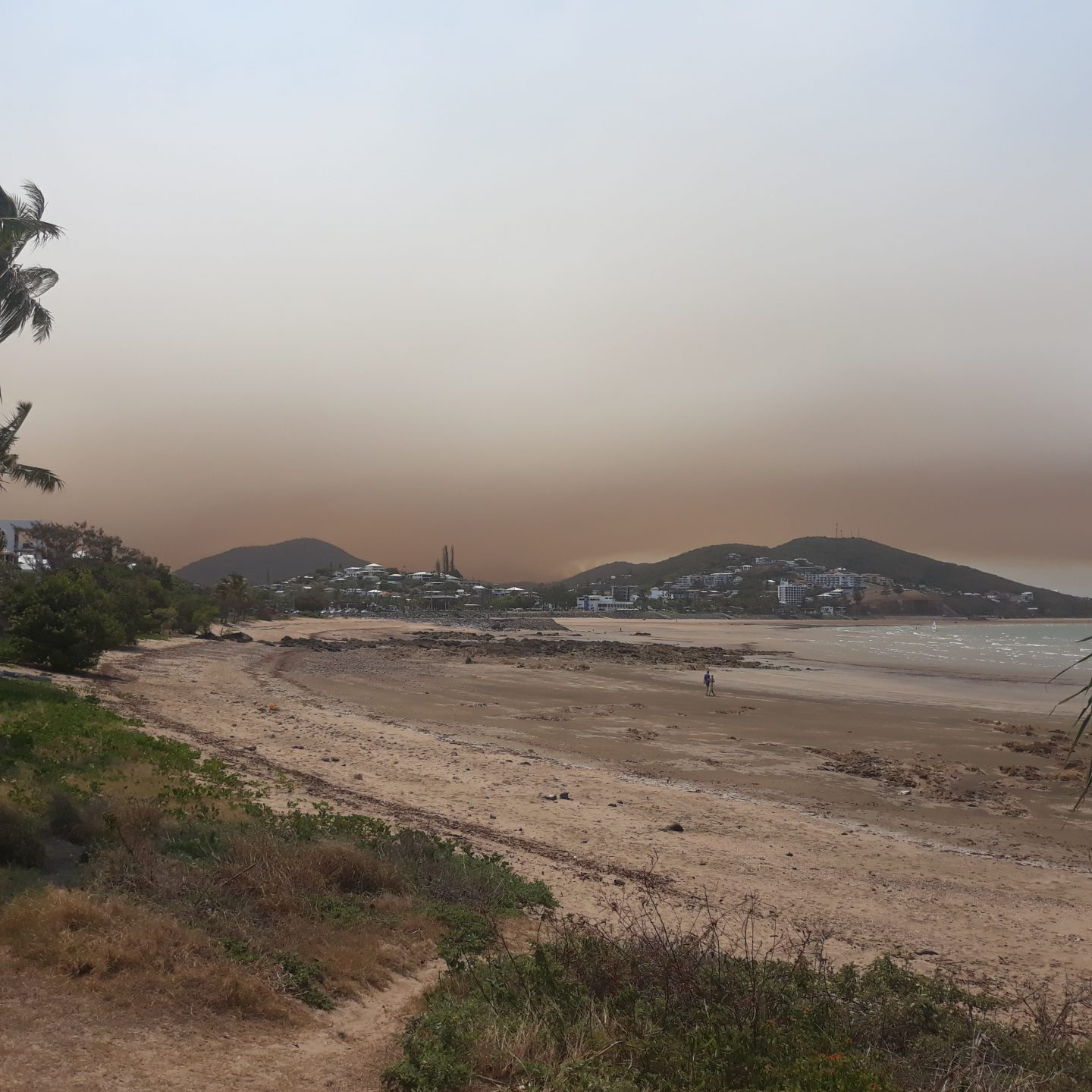 A beach with a large smoke plume in the distance.