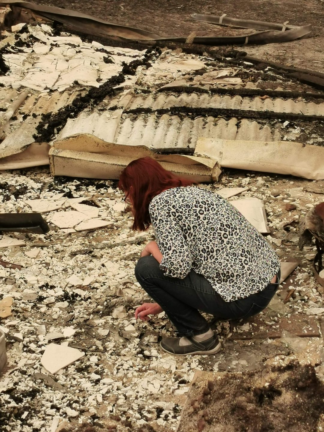 A woman squatting down over rubble from an extinguished bush fire.