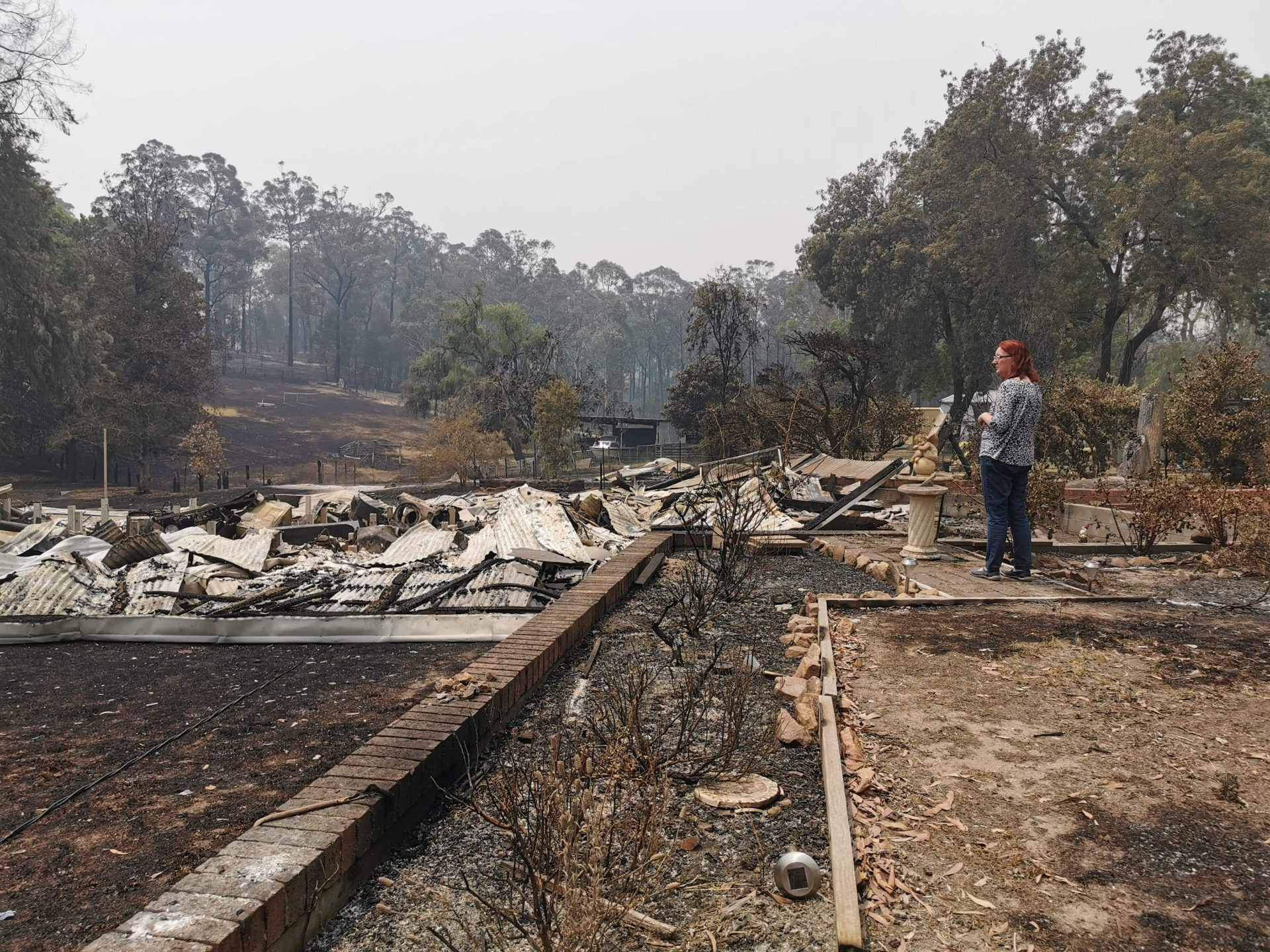 A woman looking over rubble from a property destroyed by a bush fire.
