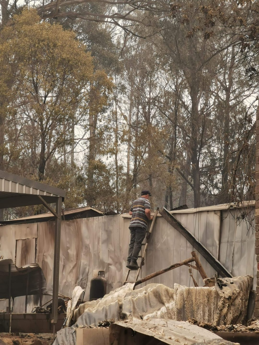 A man standing on a latter leaning against a wall on a property that has been damaged by bush fire.