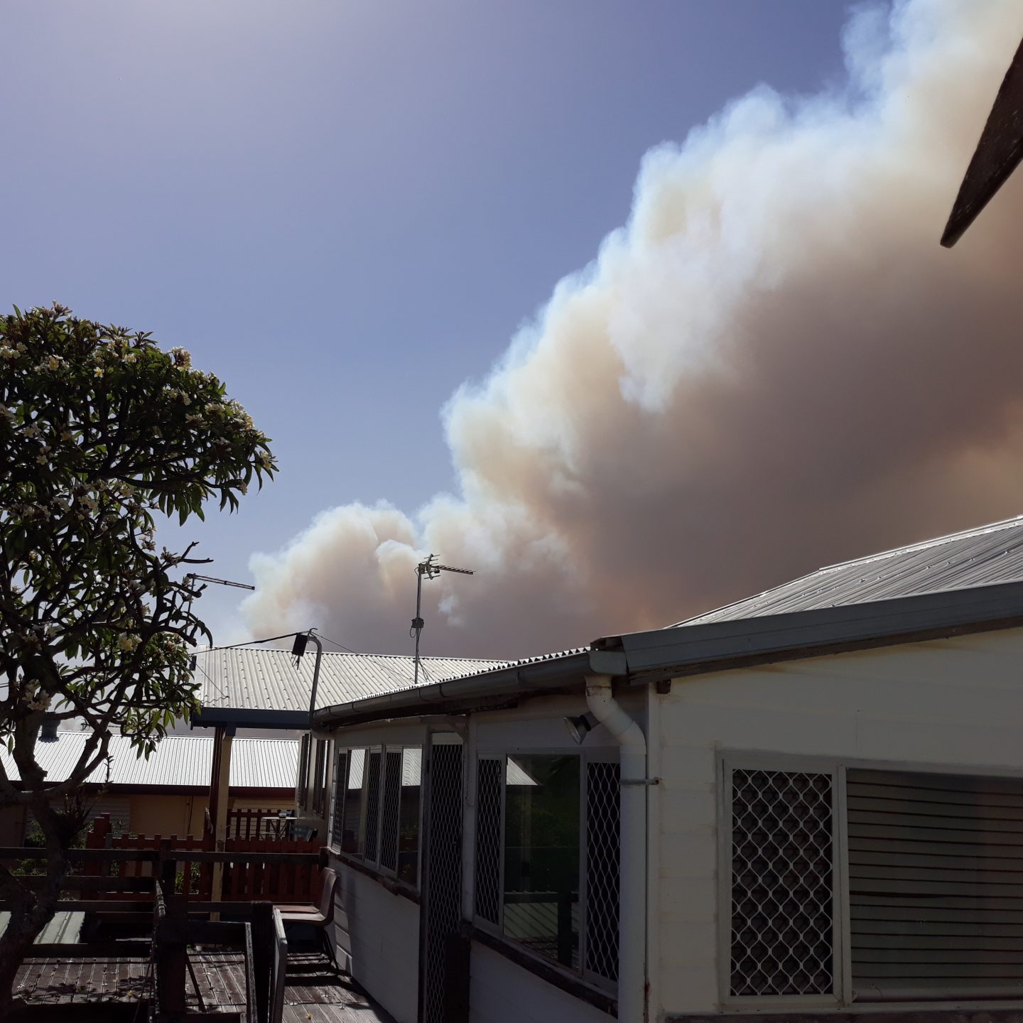 A house with a large plume of smoke emerging from behind it.