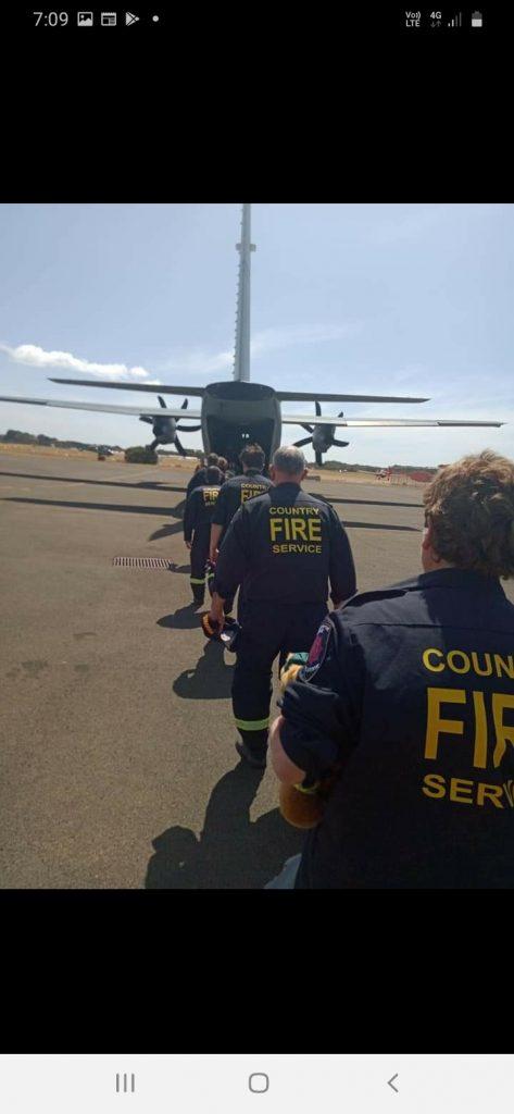 Fire personnel walking across a tarmac towards a plane before a flight.
