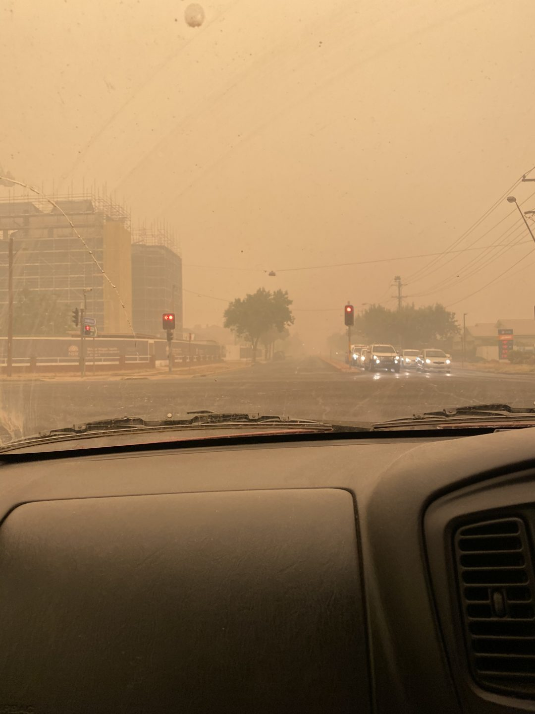 A photograph taken from inside a car looking at bushfire smoke covering the city of Wagga Wagga