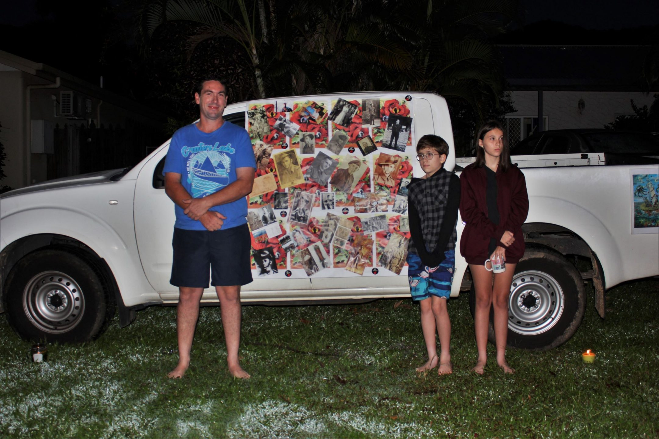 Man, boy and girl standing beside a vehicle with collage attached to its side. Taken before dawn.