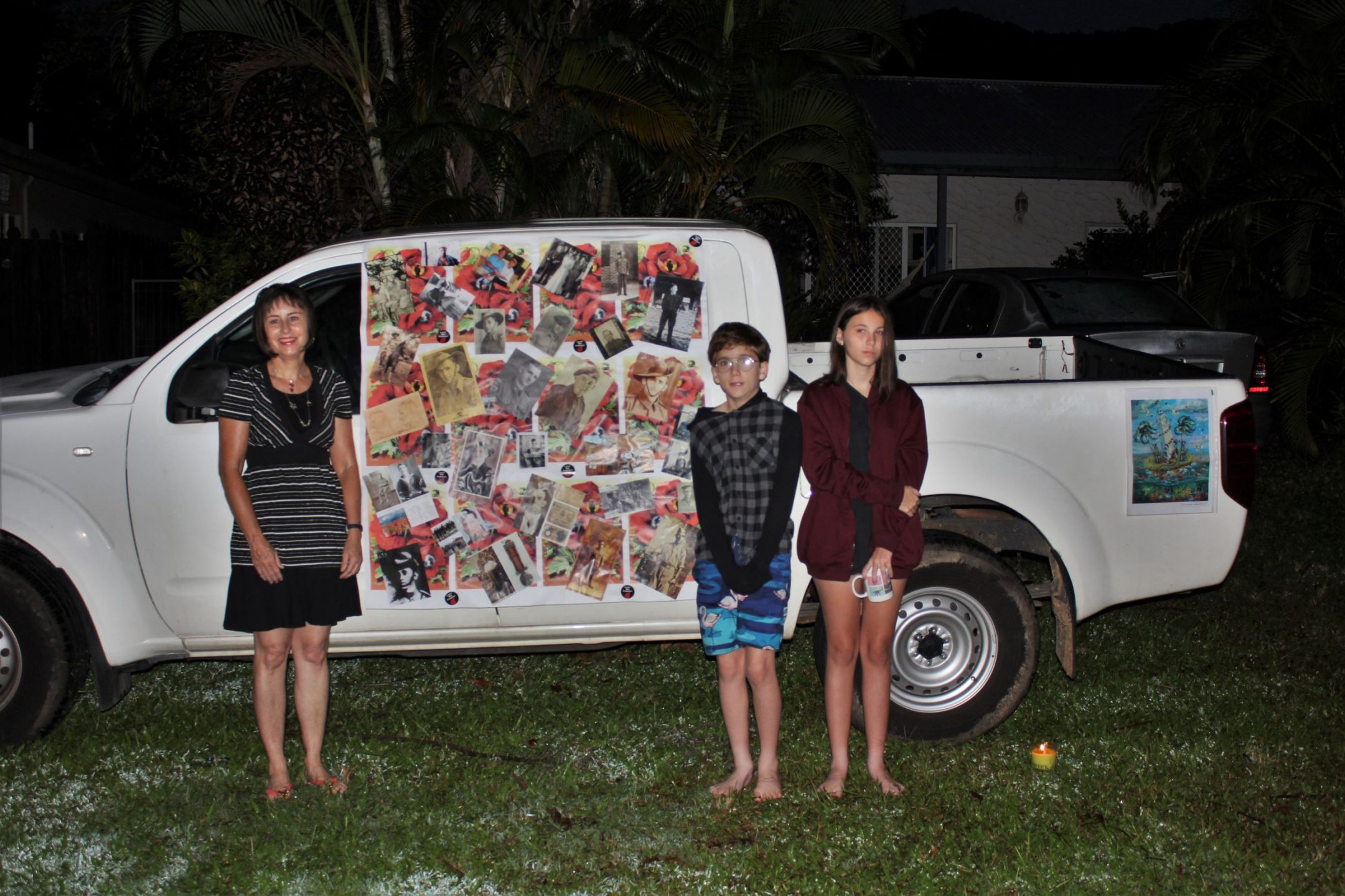 Woman, boy and girl standing beside a vehicle with collage attached to its side. Taken before dawn.
