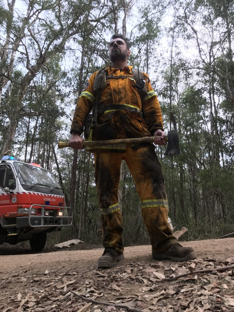 Firefighter holding axe covered in soot on a dirt road with trees in the background.