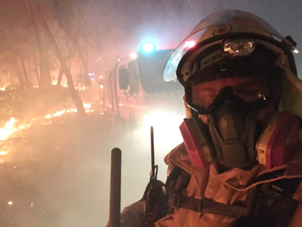Fireman wearing a mask and googles surrounded by smoke standing in front of a truck and bush land that's on fire.