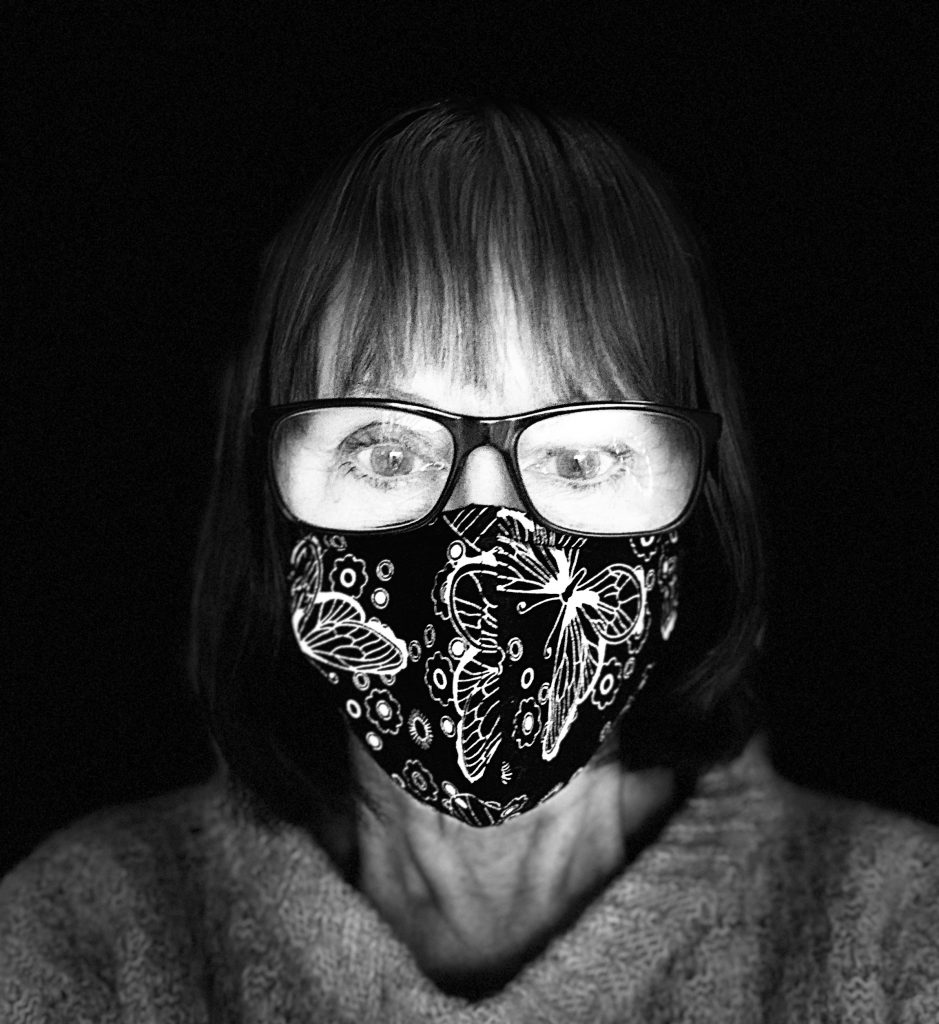 Black and white selfie of a woman wearing a glasses and a face mask.