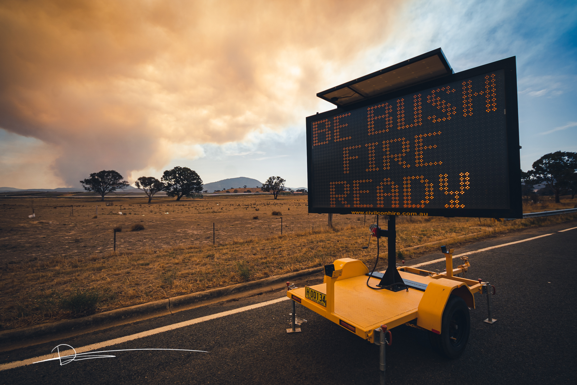 Photo shows smoke from a fire in the background, a dry paddock and a sign saying be Bushfire Ready.