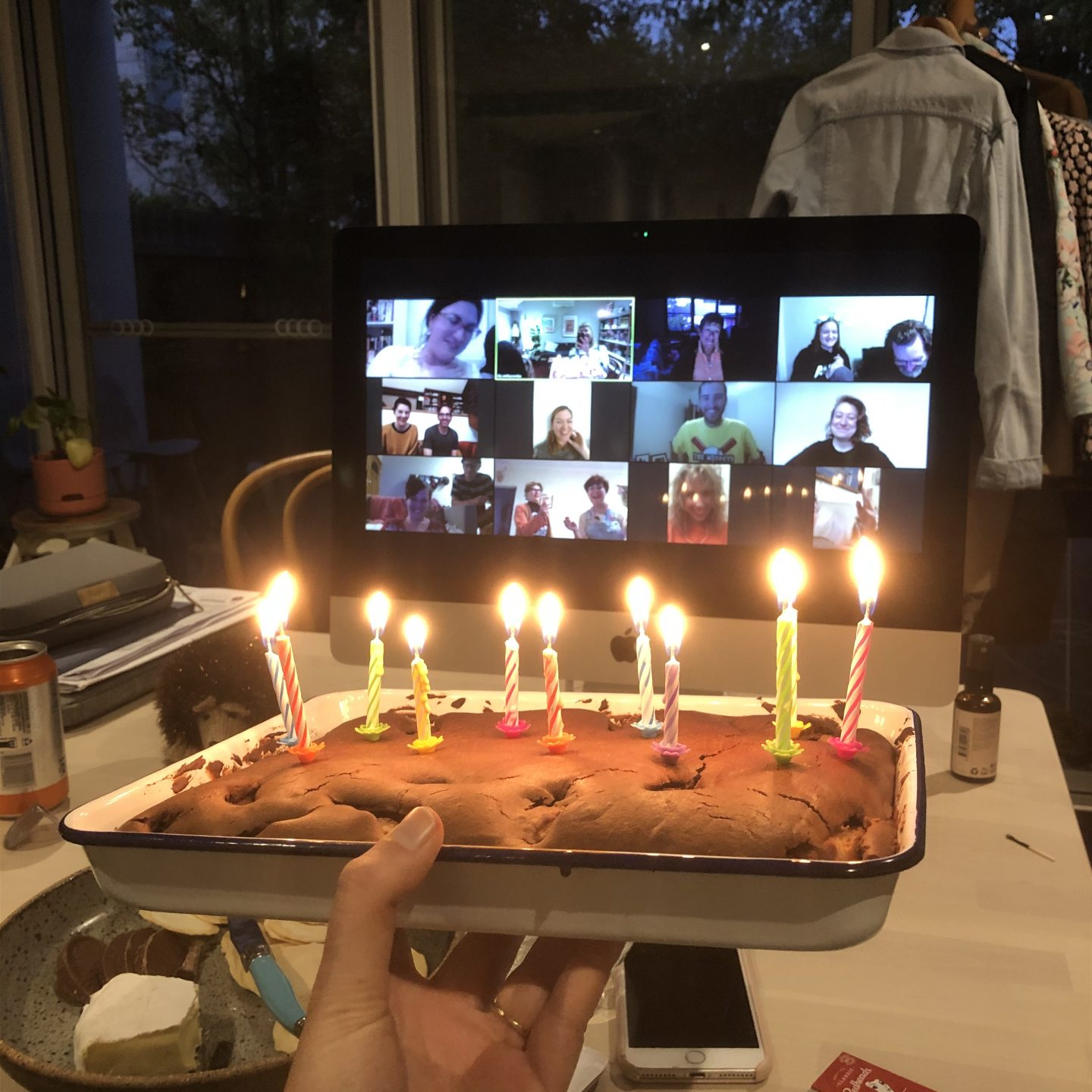 Birthday cake with ten lit candles, being held in front of a computer screen with 16 people in squares (Zoom).