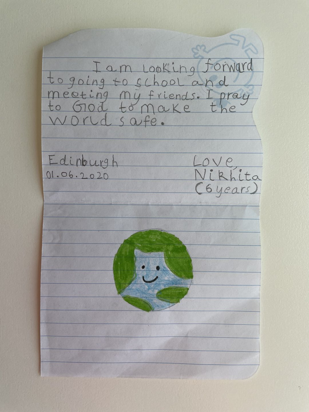 I am looking forward to going to school and meeting my friends. I pray to God to make the world safe.   Edinburgh 01.06.2020  Love,  Nikhita (6 years)  [Drawing of the world with a smiley face]