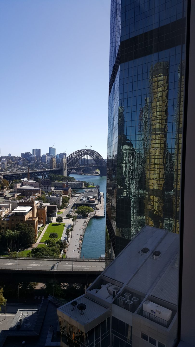 a view to Sydney harbour from a hotel window. In the distance is the Sydney harbour bridge.