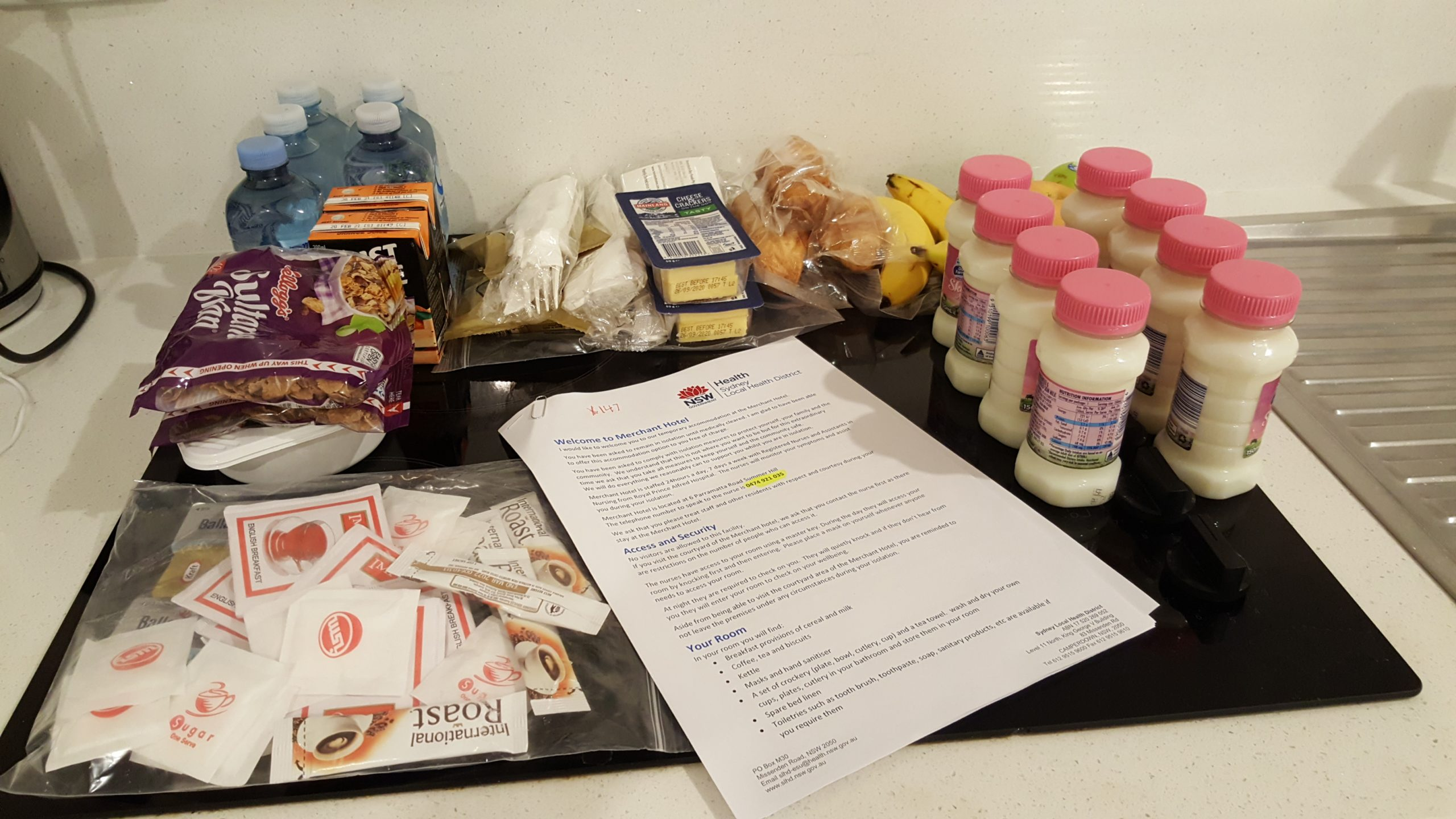 a care packaage receievd furing hotel quarantine including bottles of milk, cereal, cheese, bread and water.