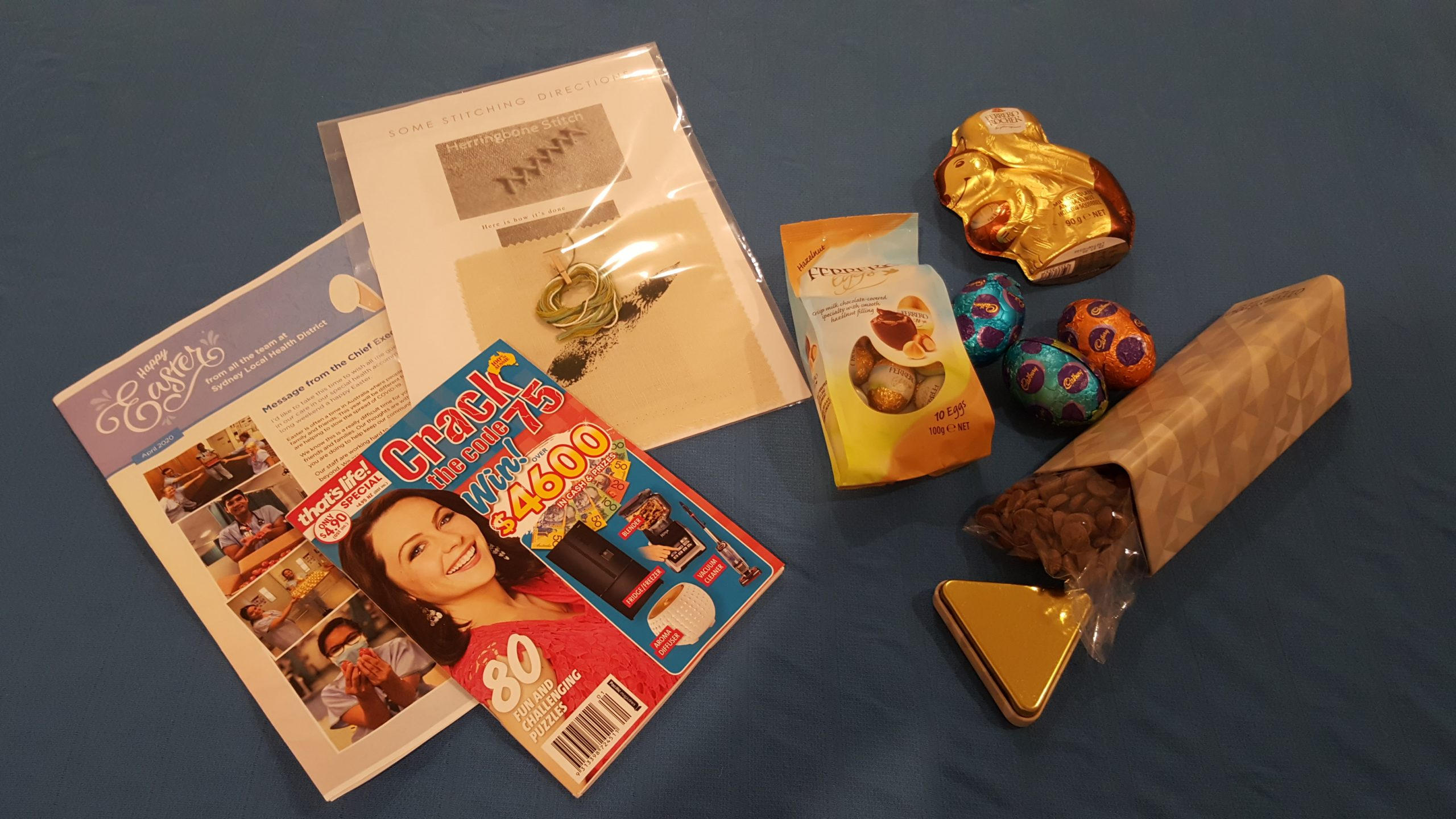 A care package received while in hotel quarantine including embroidery kit, puzzle and books
