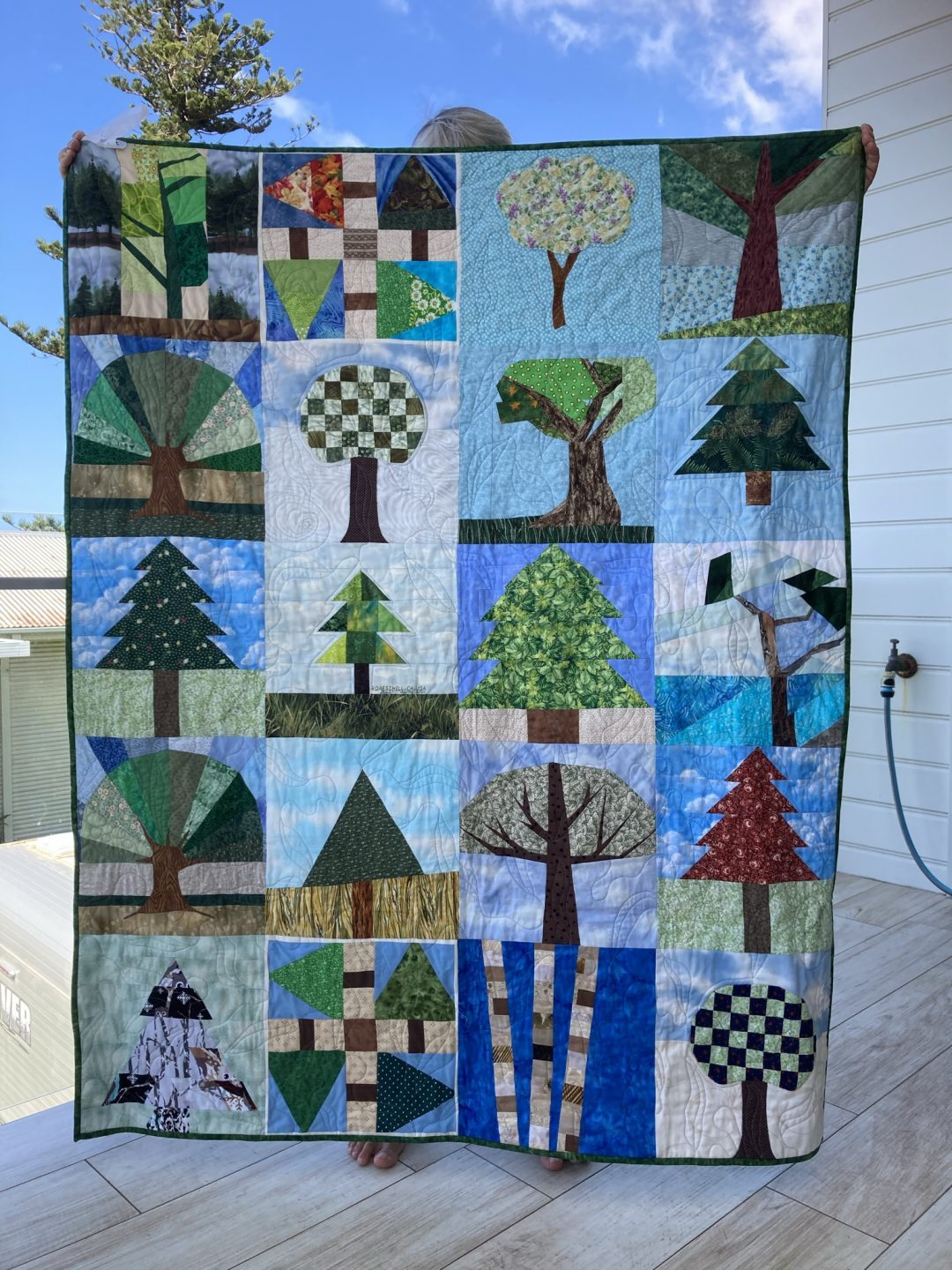 A full quilt being held up. Each panel shows a different tree in a different season. Colours are green, blue, red, black and white.