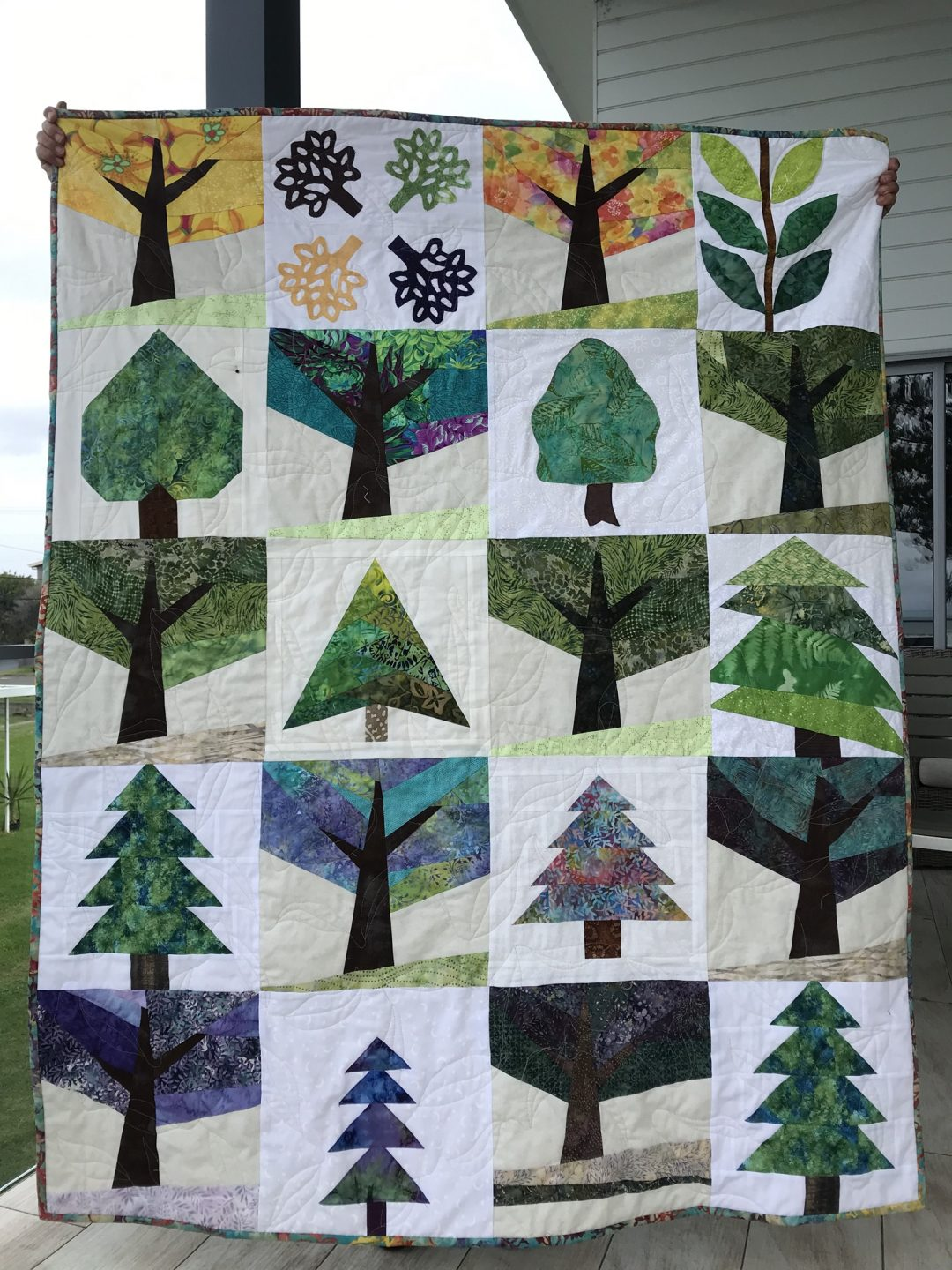 A full quilt being held up. Each panel shows a different tree in a different season. Colours are green, blue, yellow, black and white.