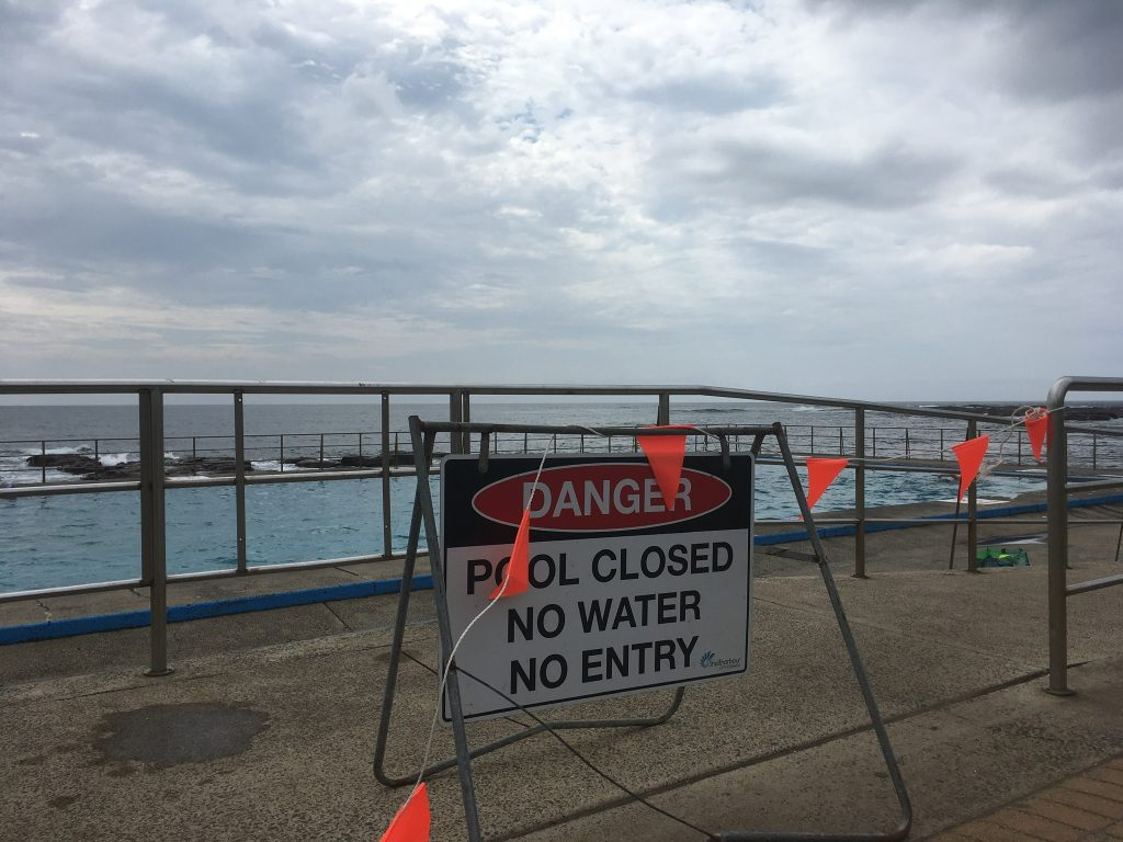 Image of an ocean pool under an overcast sky. There is a sign in front reading 'DANGER. POOL CLOSED. NO WATER. NO ENTRY' with orange warning flags draped over the sign.