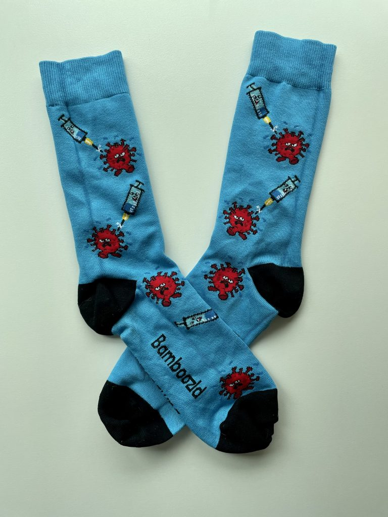 Two socks. The left is placed over the right. Both are bright blue, with black toes and heels, with repeating decoration of a red virus and a blue syringe facing towards it.