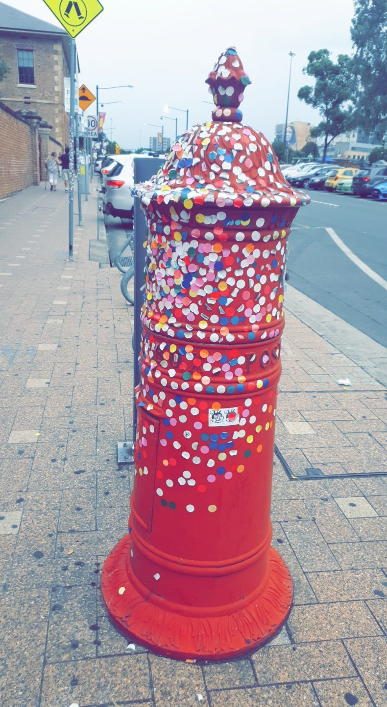 Red post box covered in round coloured stickers