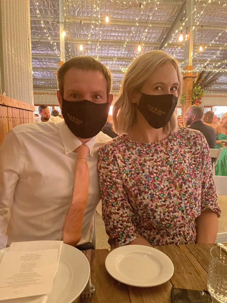 a couple at a wedding with black face masks on.