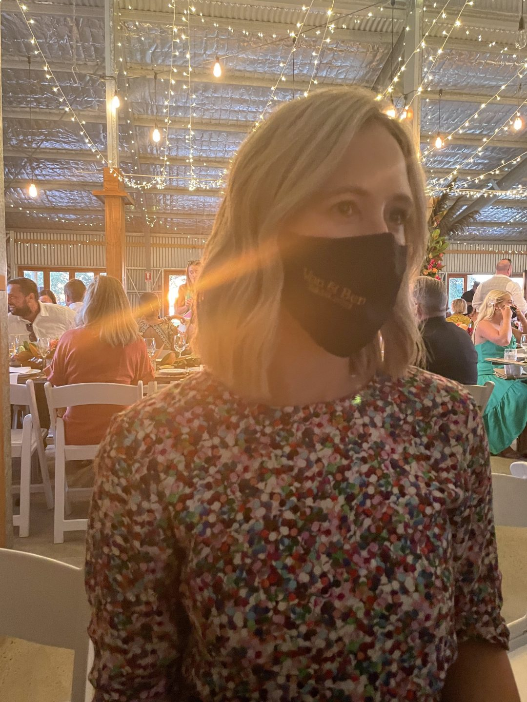 a woman with blonde hair at a wedding with a black face mask on.