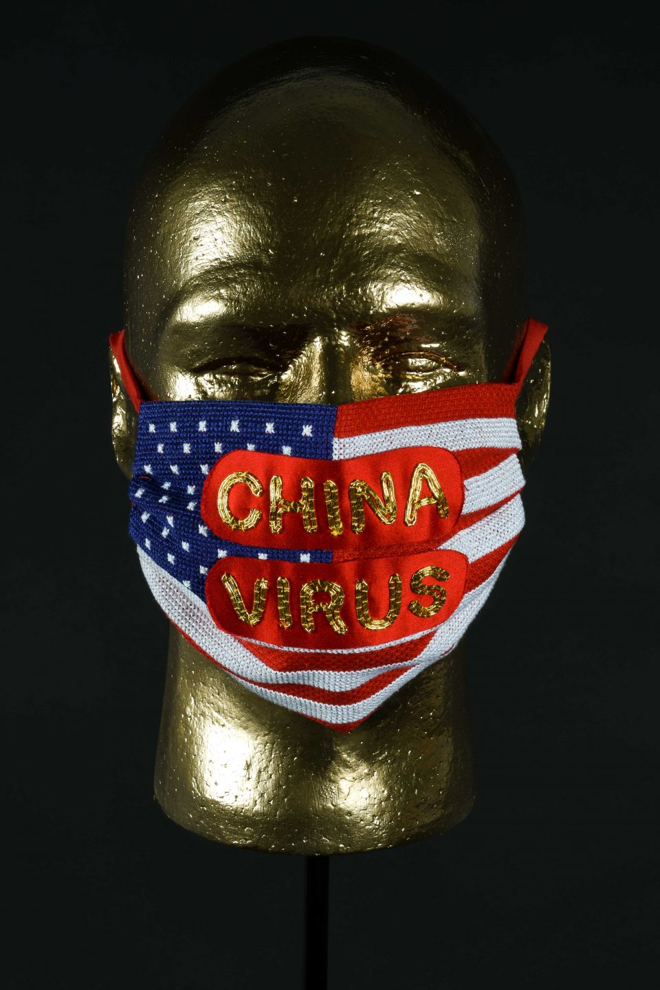Golden mannequin head with a handstiched mask featuring the American flag overlaid with red satin with China Virus stitched on top.