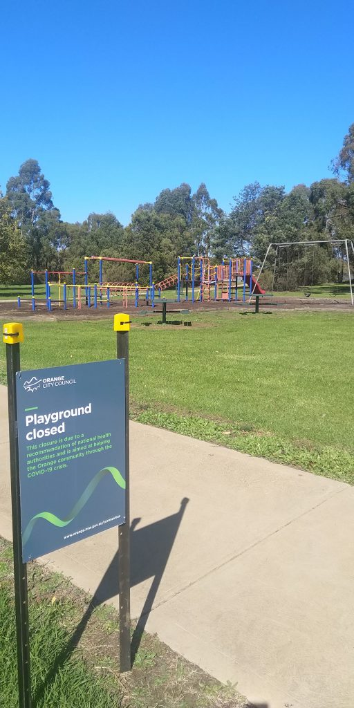 A sign that says 'playground closed' and an empty playground behind it.