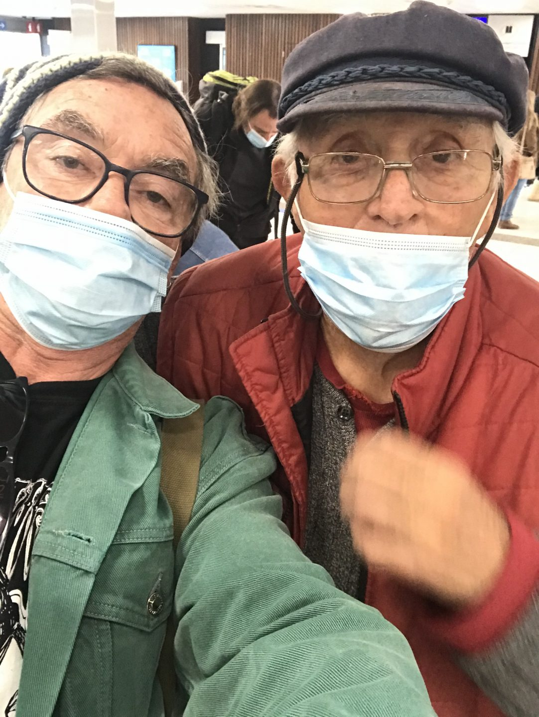 Two caucasian men, both wearing blue surgical masks. A selfie. Both are wearing hats. One has black glasses and a green jacket. The other silver glasses and a red jacket.