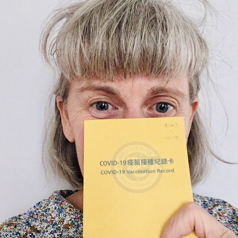 Photo of a woman with a blonde fringe holding up a yellow vaccination card over her face with Taiwanese script, reading 'COVID-19 vaccination Record'
