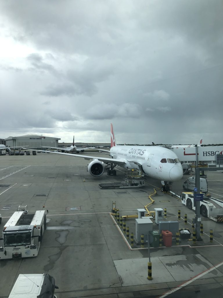 a QANTAS plane at Heathrow airport, against a grey and cloudy sky