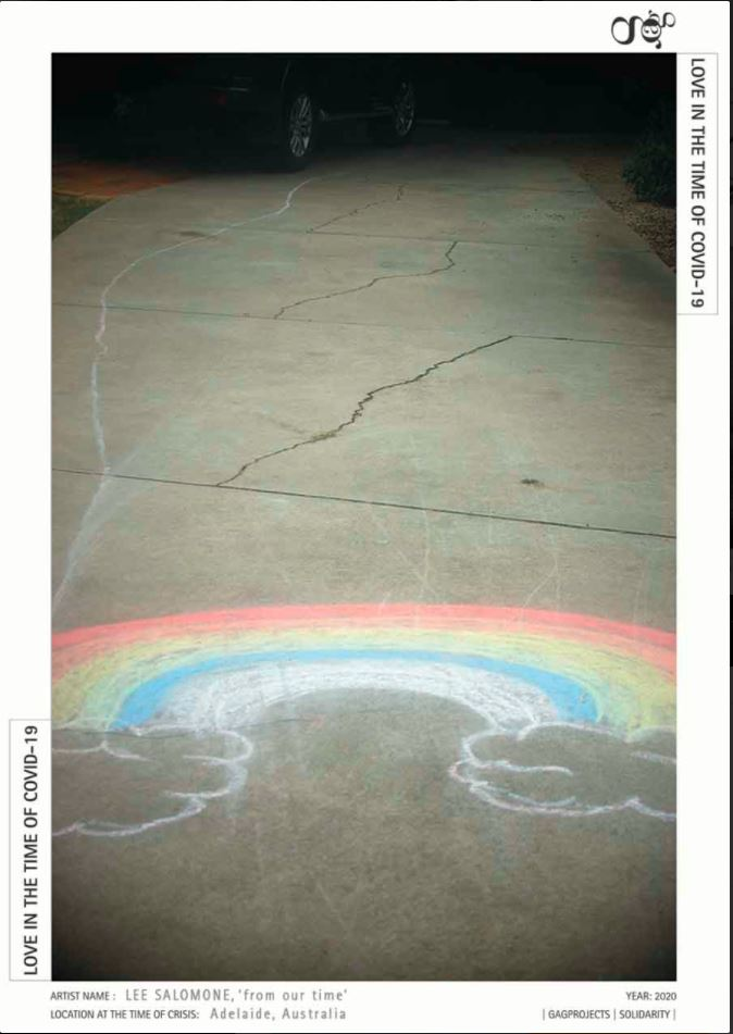 A colourful chalk drawing of a rainbow decorates a concrete pavement, while at the far edges of the work are the wheels of a shadowy car in darkness.