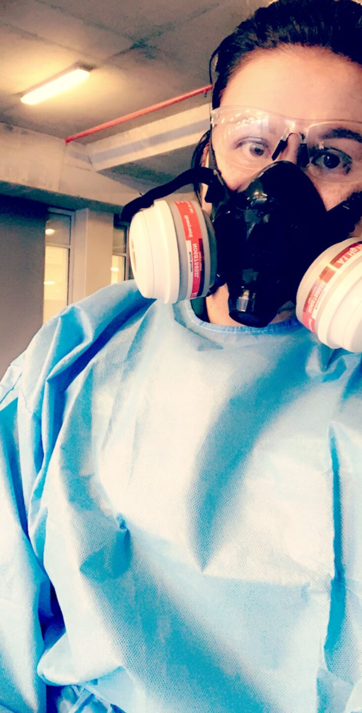a photo of a paramedic wearing a blue protective suit, a face mask and transparent goggles.