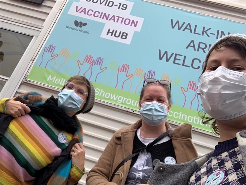 A selfie featuring three women wearing casual winter clothes and blue surgical masks, in front of a sign reading 'COVID-19 VACCINATION HUB/ WALK-INS ARE WELCOME'