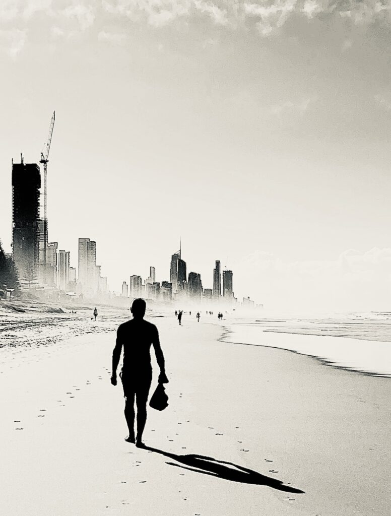 a silhouette of a man walking on a beach with tall buildings to his left.